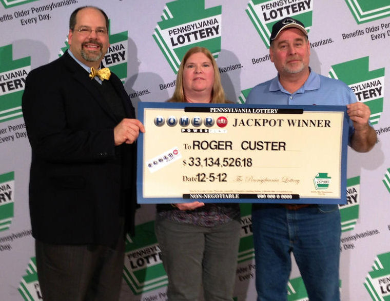 Roger Custer, right, and his wife accept the check from Powerball officials.