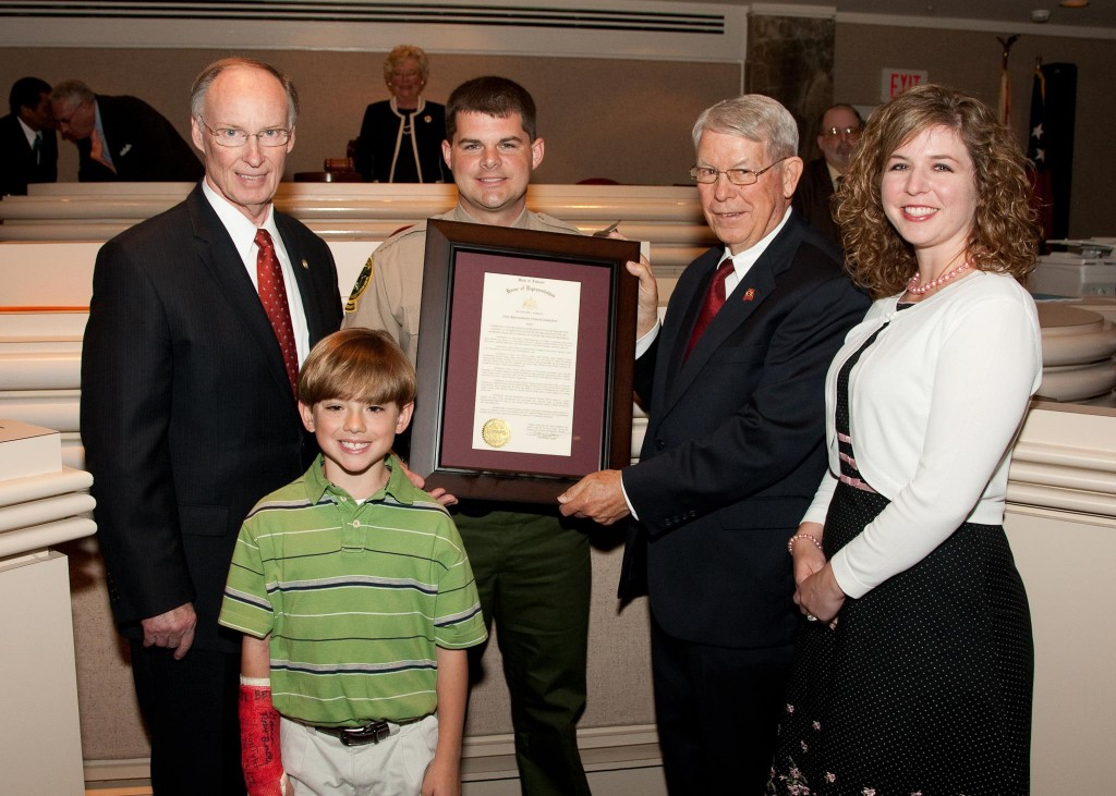 Alabama Conservation Officer receives the state legislature's top honor from Rep. Howard Sandifer, as Gov. Robert Bentley and Lindsey's son XXX and his wife XXXX.