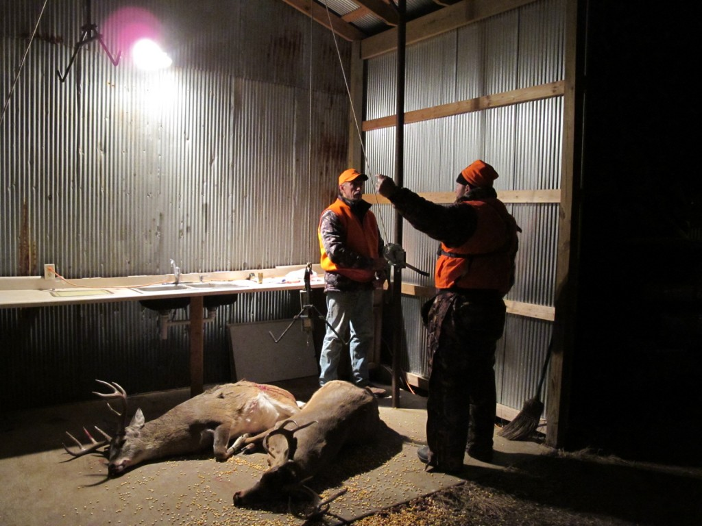 Shane Alexander of Montana explains to Tall Tine Outfitters owner Ted Jaycox what he'd seen in the stand that afternoon, as two bucks on the floor are ready for skinning.