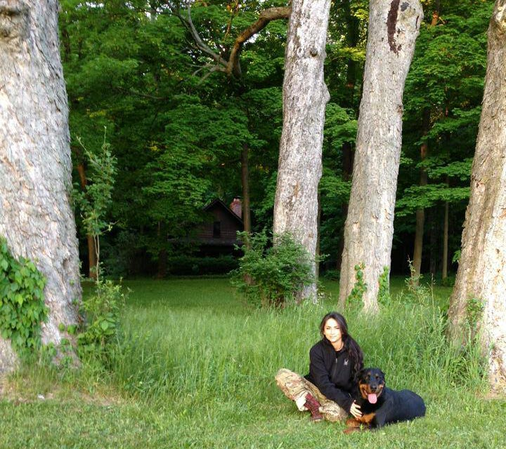 Nicole McClain sits in the woods with her Rottweiler Mogador Frankenstein McClain