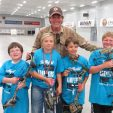 Ted with kids at indoor bow shoot helping them learn about archery and the fun of shooting a bow.