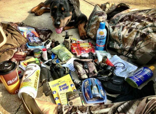 Hunter Nicole McClain sorts through hunting gear with her Rottweiler, Mogador